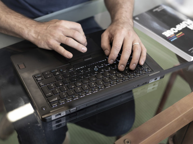 Typing Business Report on Laptop